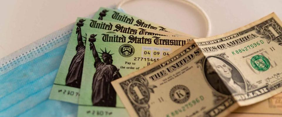 Washington, usa - 10 march 2021: close up of stimulus check and face mask and banknote on black background, concept of federal financial help given to stop economic crisis on white background