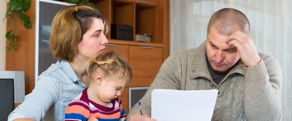Serious couple with little girl counting budget at home.