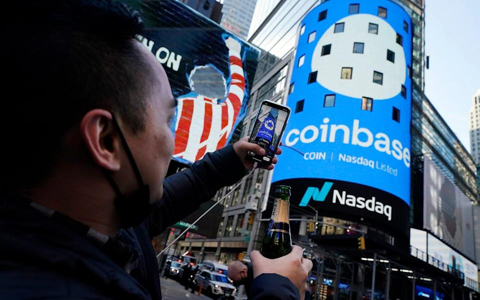 Coinbase employee Daniel Huynh holds a celebratory bottle of champagne outside the Nasdaq MarketSite on the day the digital currency exchange becoming a publicly traded company - Richard Drew/AP