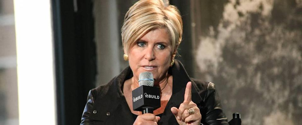 Suze Orman holds a microphone and points her finger at someone off camera
