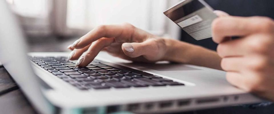 Hand holding credit card and using laptop. Businesswoman or entrepreneur working from home. Online shopping, e-commerce, internet banking, spending money, work from home concept