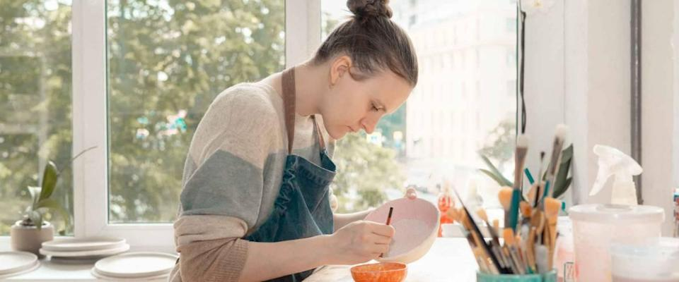 Young woman in apron sitting at table and drawing on ceramic bowl.