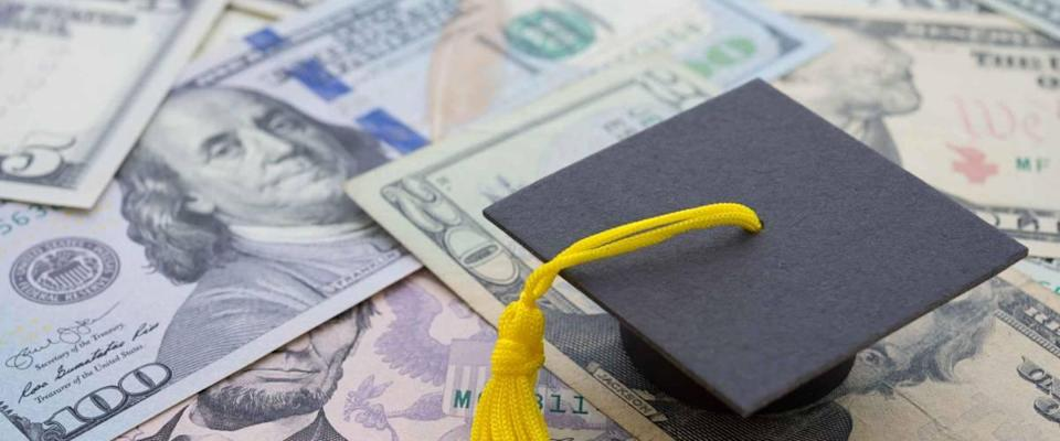Graduation cap university or college degree on US dollars banknotes background. Education expense budget plan of money saving, loan, debt, personal loan