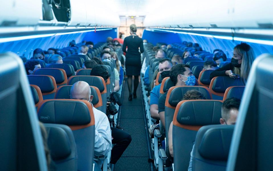 Passengers wearing protective masks are seen aboard before a JetBlue flight to London at JFK International Airport - JEENAH MOON/REUTERS