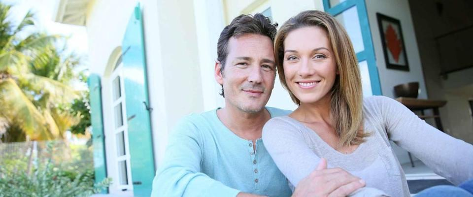 Middle-aged couple sitting on house front door