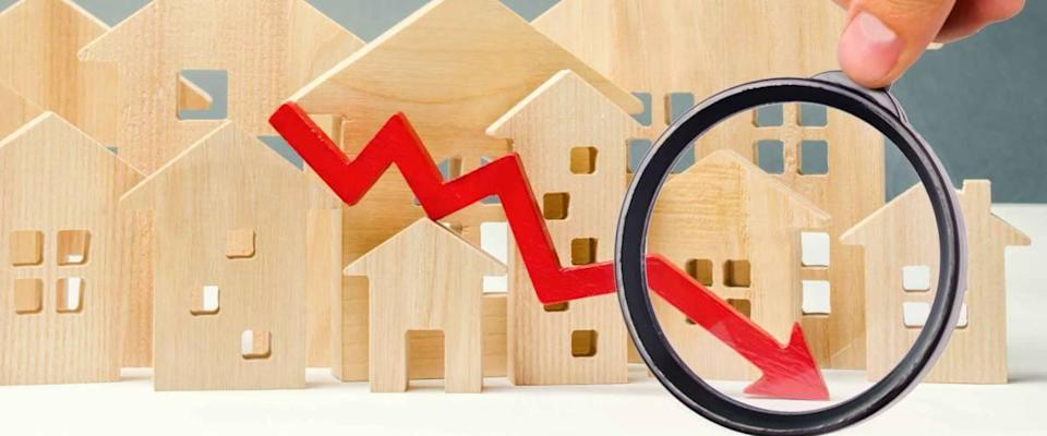 The concept of falling real estate market. Reduced interest in the mortgage. Small wooden homes with red down arrow.