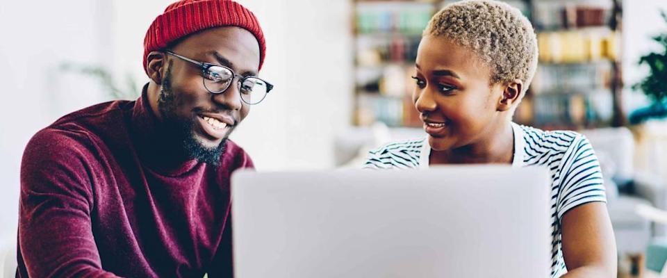 African american couple browse website on laptop computer, looking for low mortgage rates.