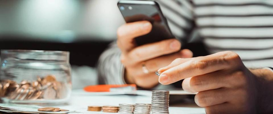 Close up on hands holding cell phone and stacking change
