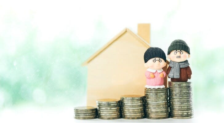 elderly couple dolls on top of a stack of coins